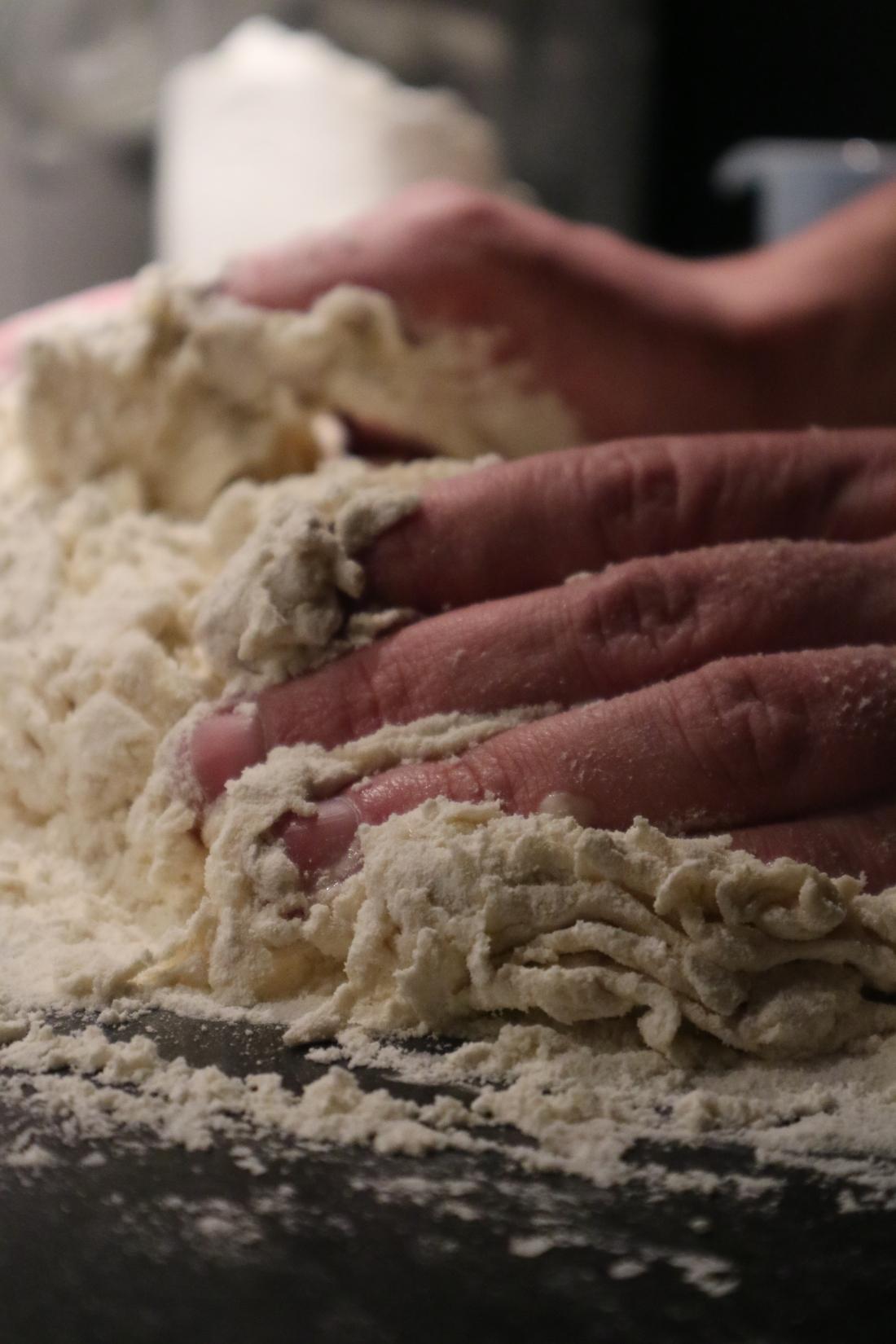 Close up van handen en brooddeeg